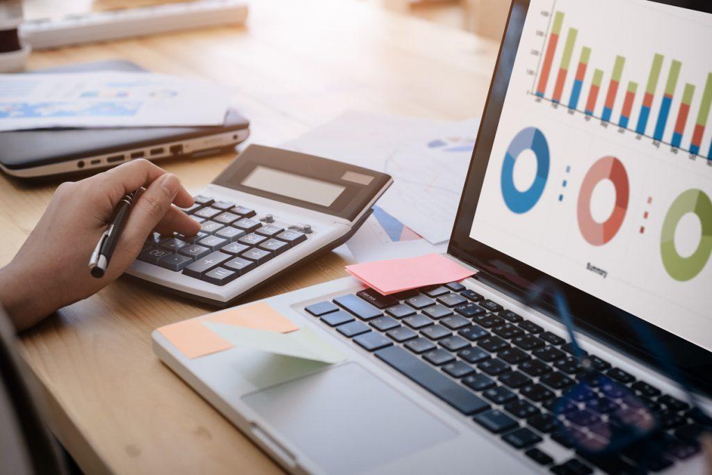 Foto de uma calculadora e notebook, com os quais está sendo feito o cálculo do preço de gestão de redes sociais
