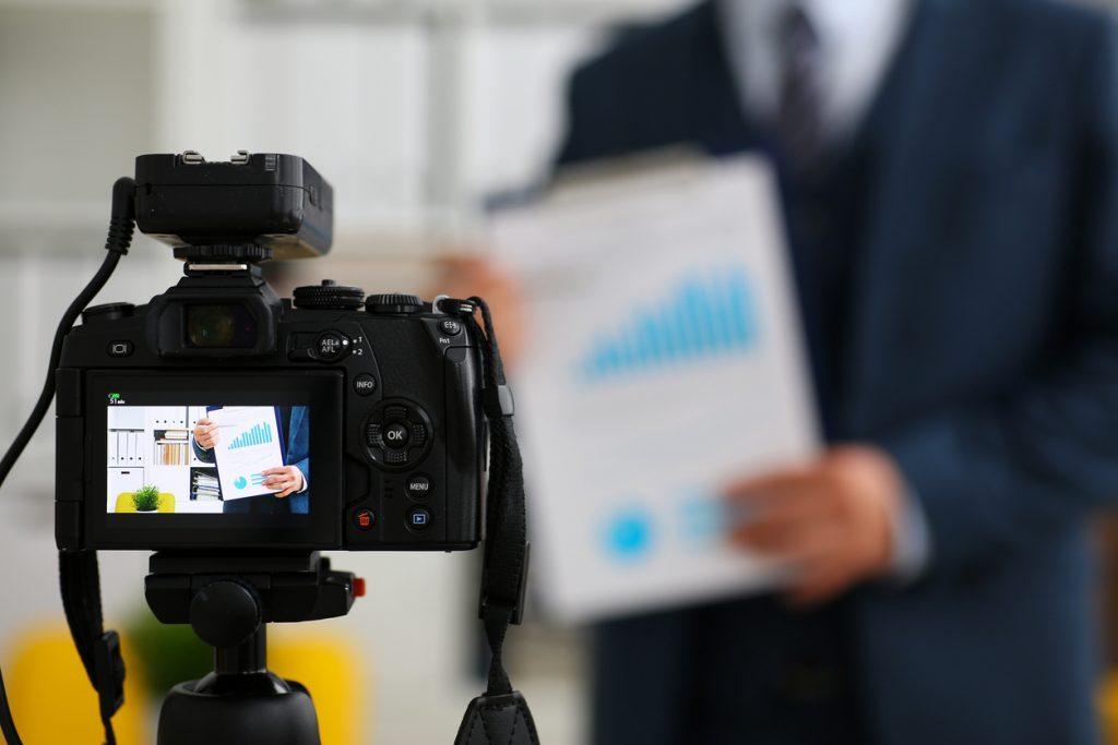 Foto de câmera gravando vídeo marketing. Homem de terno ao fundo segurando um relatório