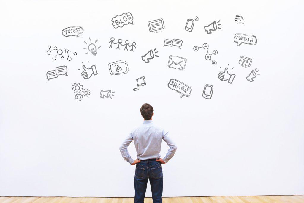 Foto de homem olhando para a ilustração de diversas formas de anunciar em marketing digital para moda