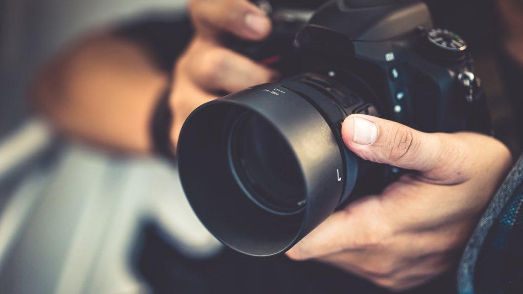 Foto de fotógrafo com câmera profissional, mostrando a importância de boas fotos para o marketing digital para moda