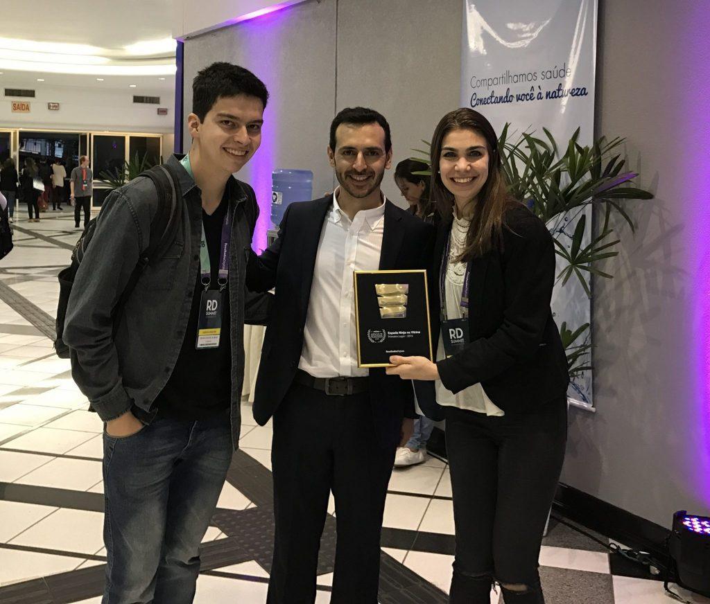Foto dos fundadores da E-dialog ao lado do CEO da Resultados Digitais com o prêmio de Espada Ninja que a agência faturou em 2018