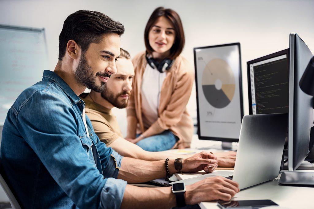 Foto de três pessoas no computador, após aprenderem como usar o Google Meu Negócio