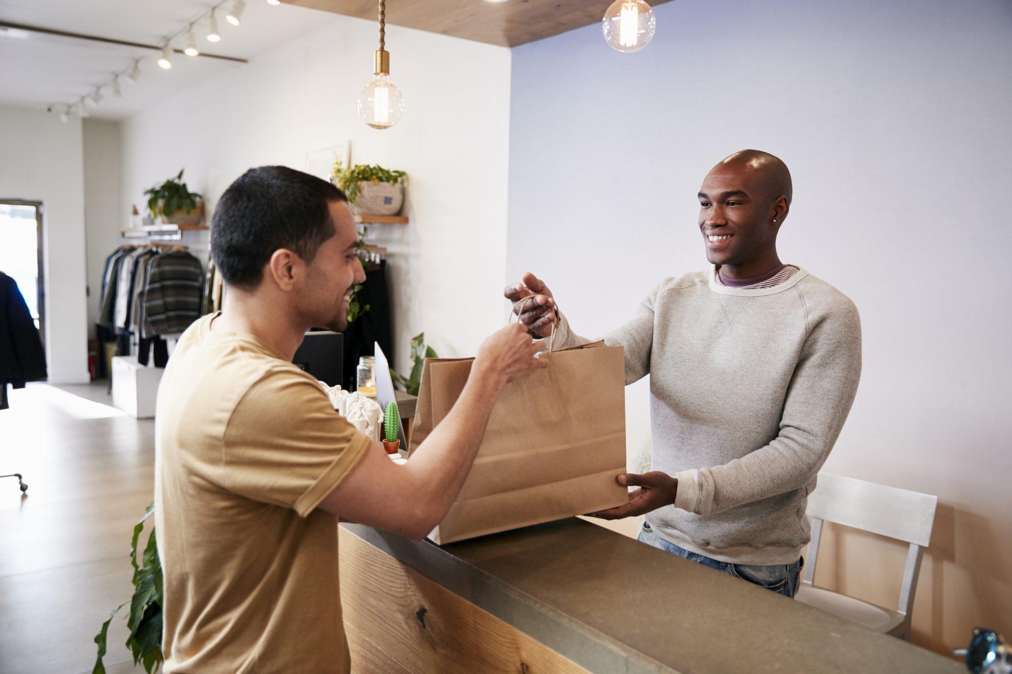 Foto de um homem fazendo compra, e o vendedor entregando a sacola. Representa o negócio local, que precisa usar a estratégia de SEO Local