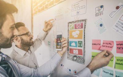 Imagem de dois profissionais planejando em um quadro físico estratégias de redes sociais que serão explicadas no blog: verba para investir em marketing digital