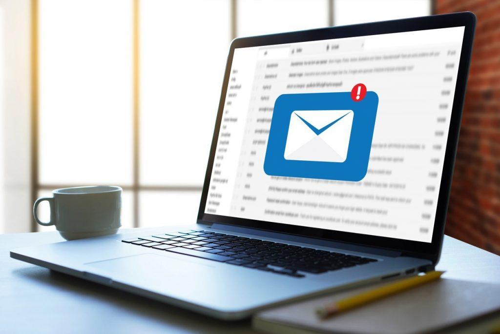 """Notebook com ícone de e-mail na tela, representando a estrategia de e-mail marketing no artigo """"O que é marketing digital?"""""""