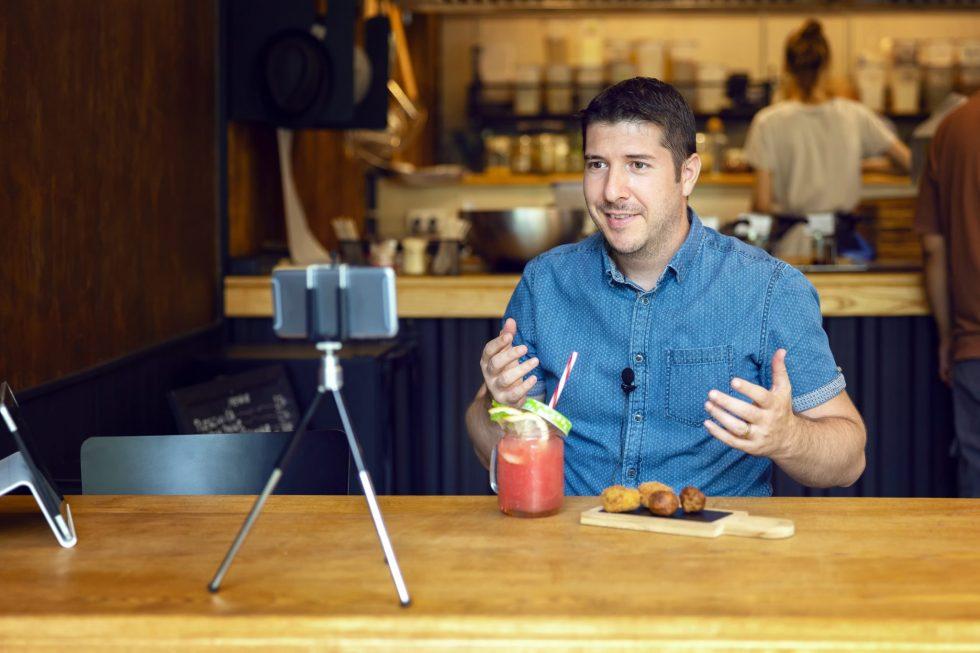 Homem de frente ao celular fazendo uma live, representação das boas práticas para um ao vivo